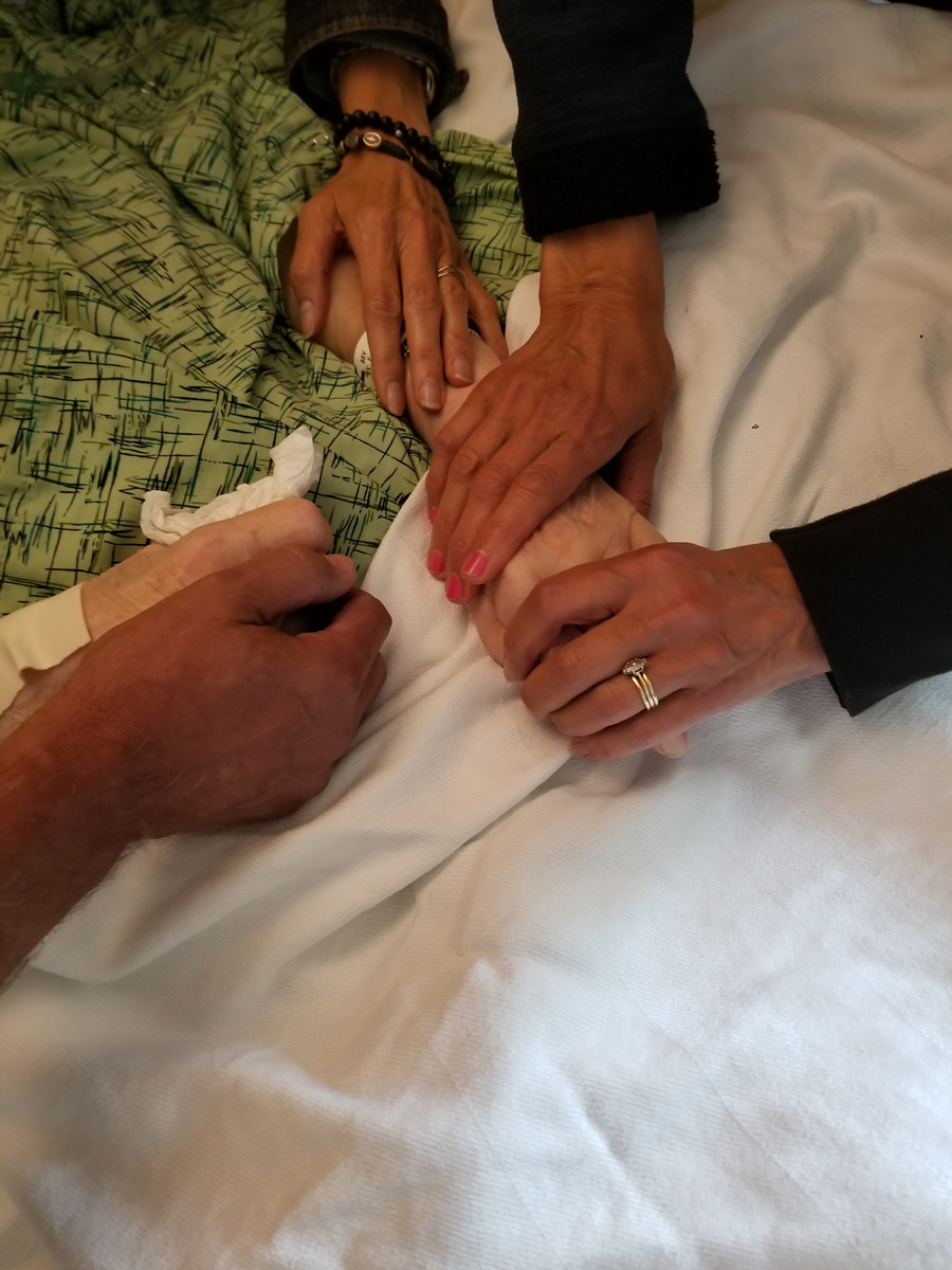 Chere Bork holding hands with her mom, Carol Meyer, at the end of her life