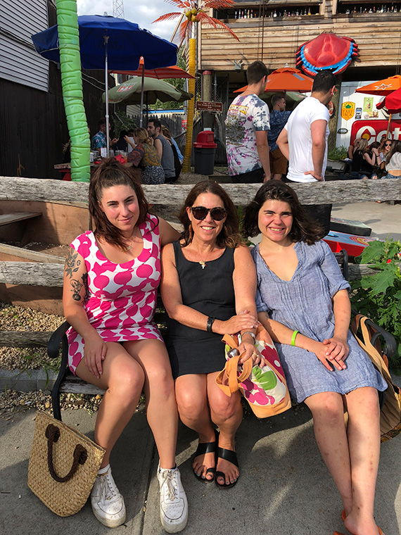Laura with her daughters, Victoria in polka dots & Isabella in blue, waiting for a table at her favorite crab house in Brooklyn, Laura's hometown.