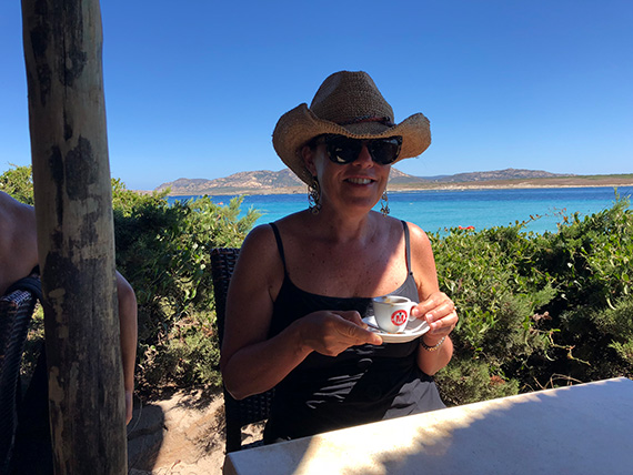 Laura enjoying an espresso at her absolute favorite place to be—the beach. This beach happens to be on Sardinia, which is a blue zone where people eat well and live long, healthy lives.