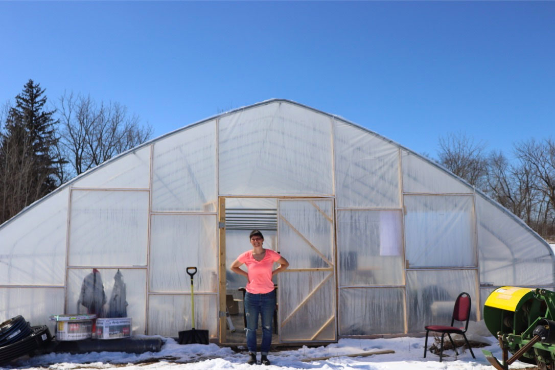 Kristin Pearson, Farmer and CSA Owner, in front of her greenhouse