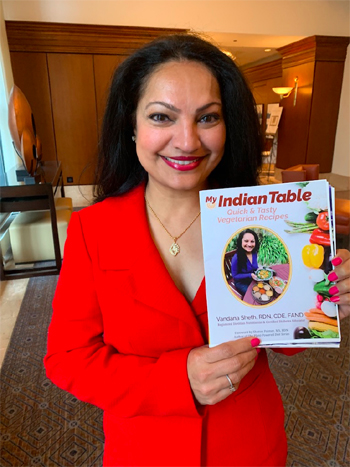 Vandana holding her cookbook