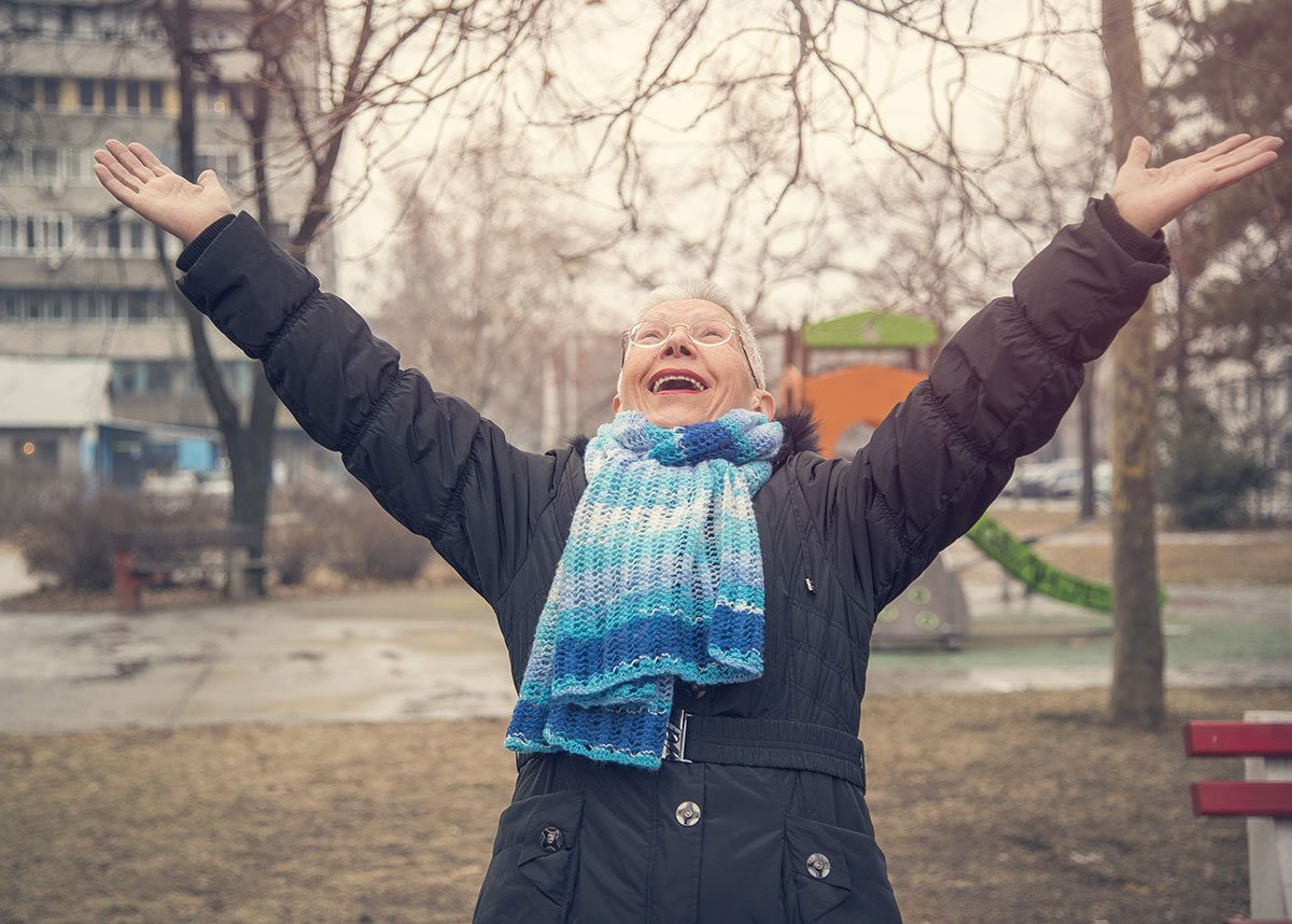 Practice gratitude to find happiness like this woman throwing wide her arms in a winter park