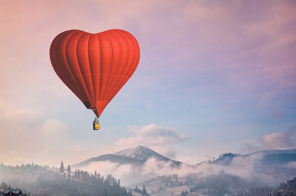 Be Your Own Valentine and Live on Purpose with No Regrets (image of red heart hot air balloon over mountain sunrise)